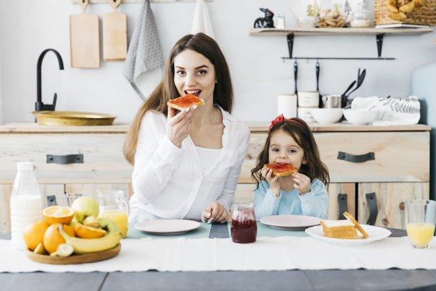 mujer-nina-desayunando-cocina_23-2148179422